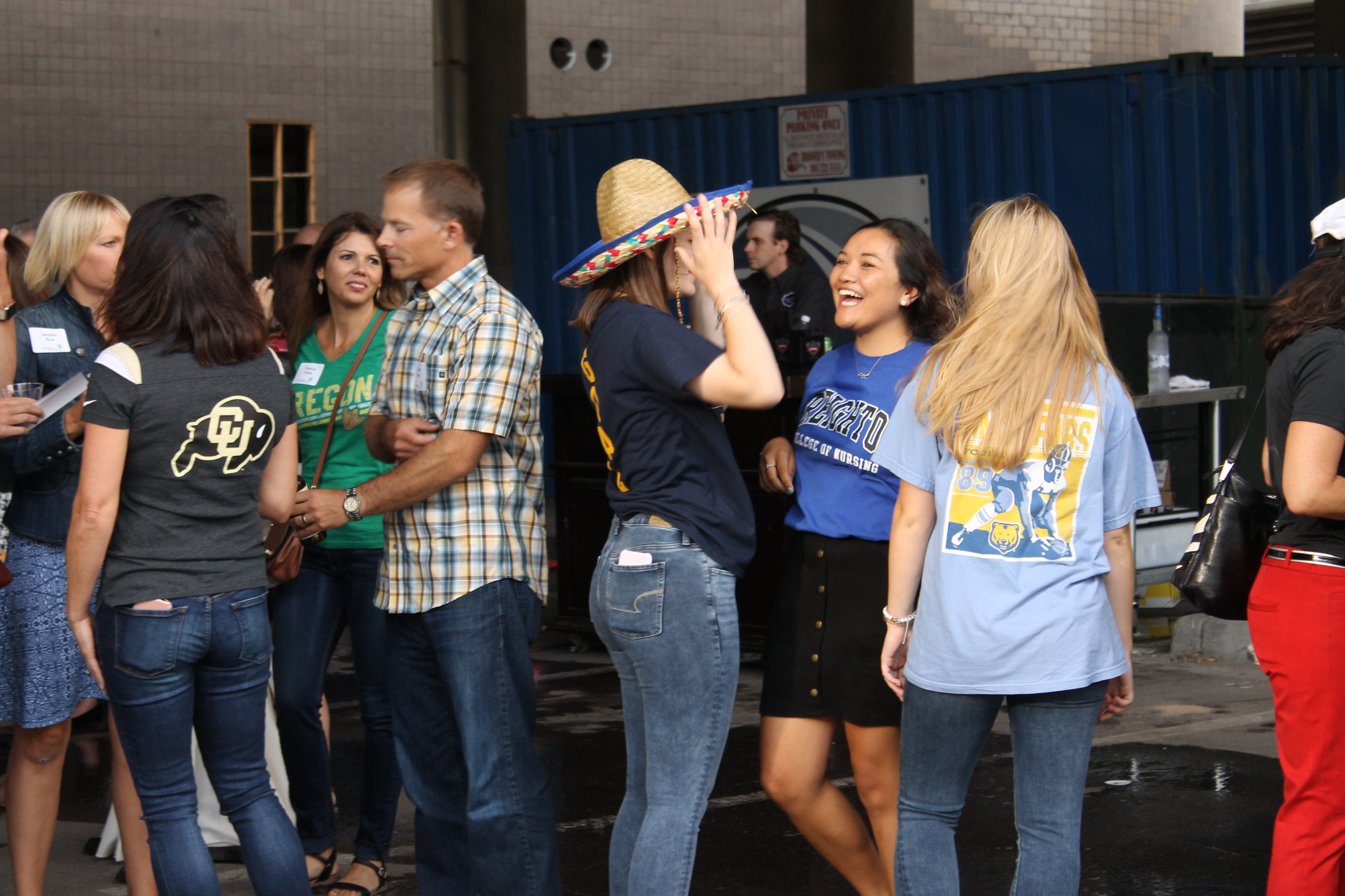 Group of people stand talking to each other in a parking lot; each wear college tshirts and jeans