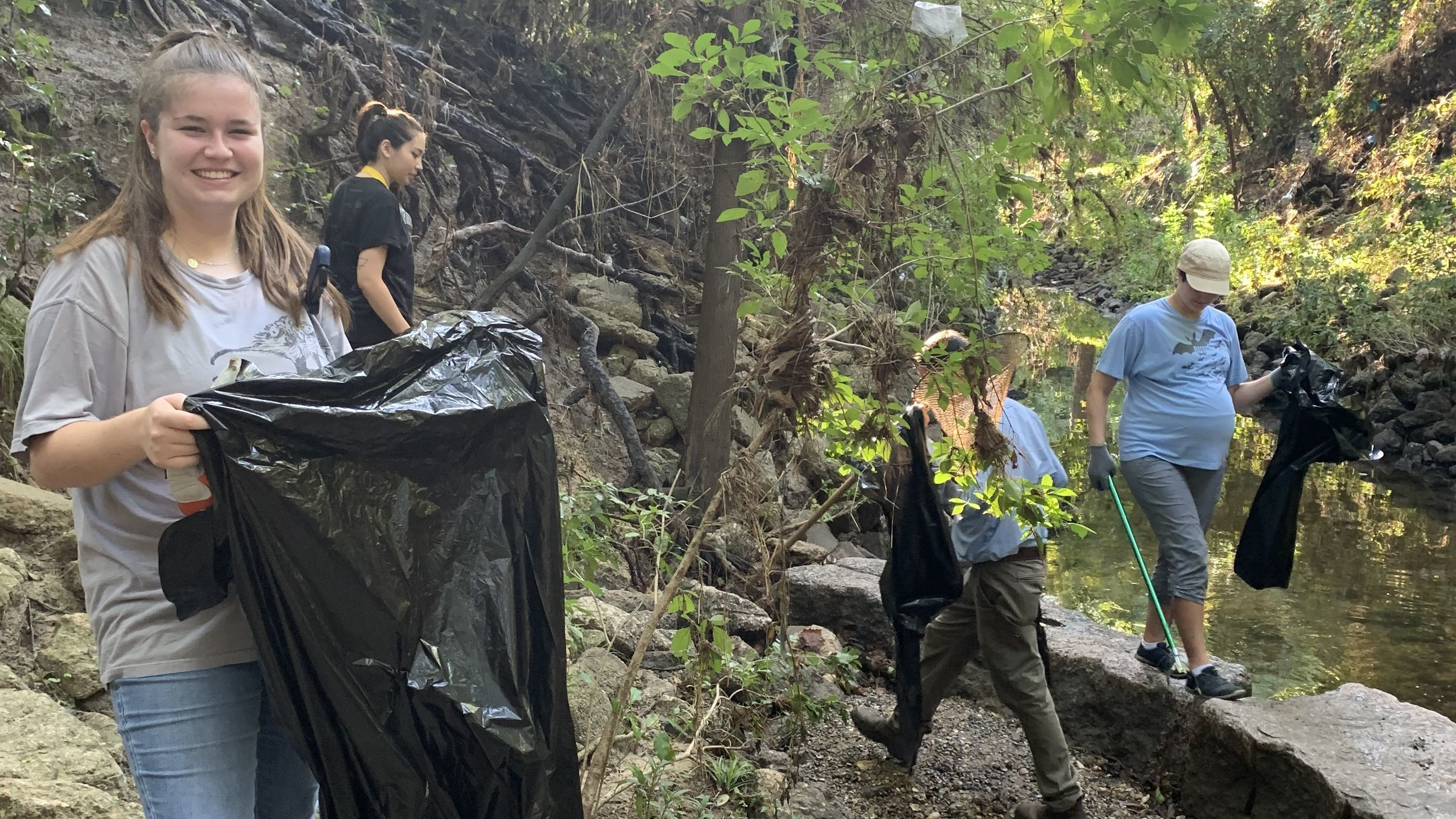 Volunteers smiling and cleaning up litter on the stream bank