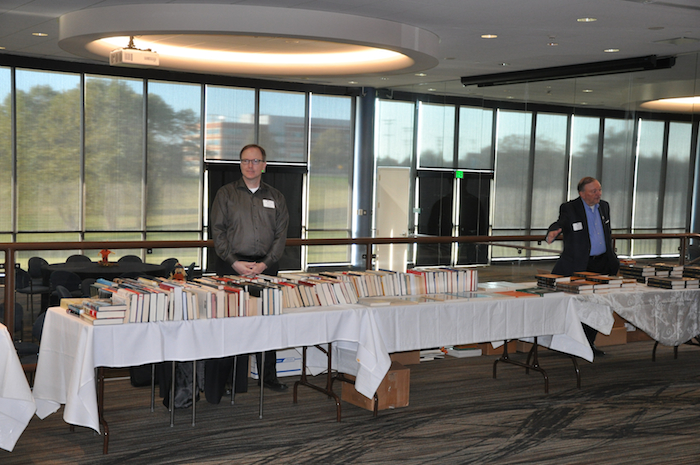 Kevin Crouse at NCMF used book sale tables and Bob Hunt at Robert Grenier and David Rohde's book signing tables.