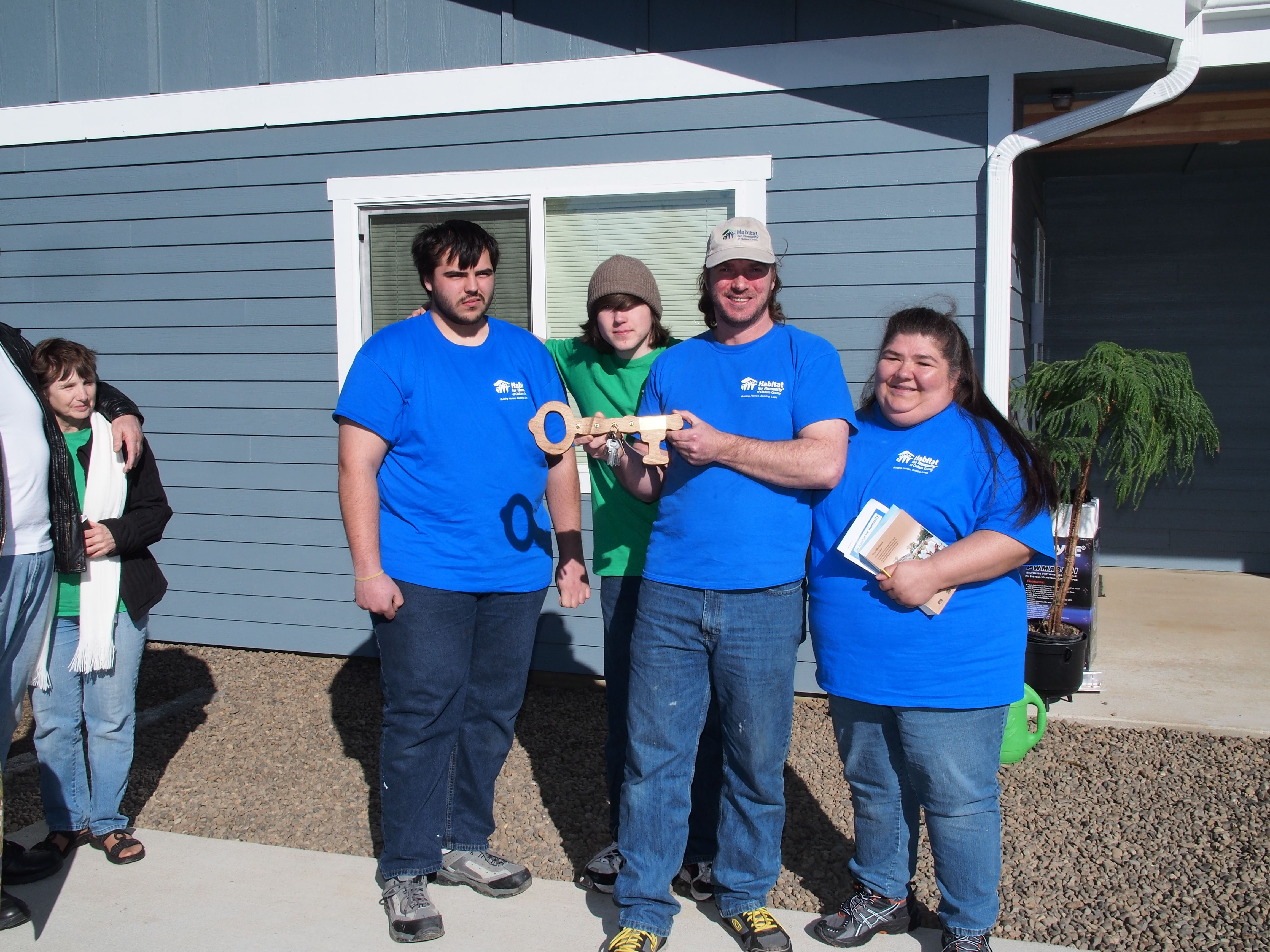 The Weaver family in front of their new home.