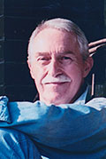 Lawrence Merritt, a man with white hair and a mustache, wearing a blue button up shirt, looking towards the camera and crossing his arms, smiling.