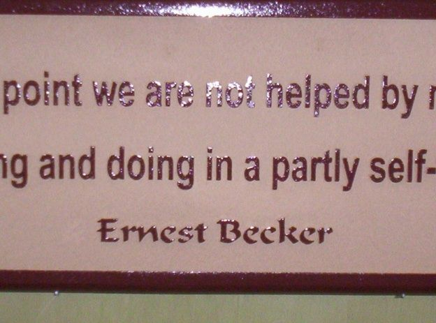 N23178 - Close-up of Carved Wall Plaque with Saying by Ernest Becker, Jewish-American cultural anthropologist and writer.