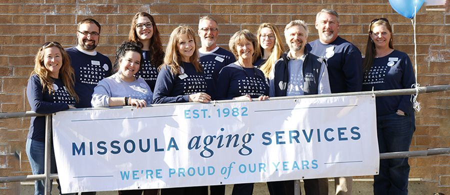 "Male and female staff smiling and holding sign that reads ""Missoula Aging Services"""