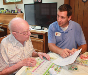 Home Health Care worker going over paperwork with older man