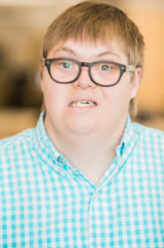 Professional photo of white man with Down syndrome smiling at camera