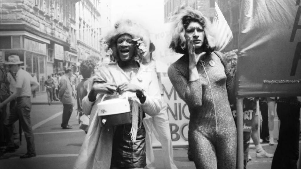 Marsha P. Johnson and Sylvia Rivera march down a street in New York City dressed in flamboyant streetwear.