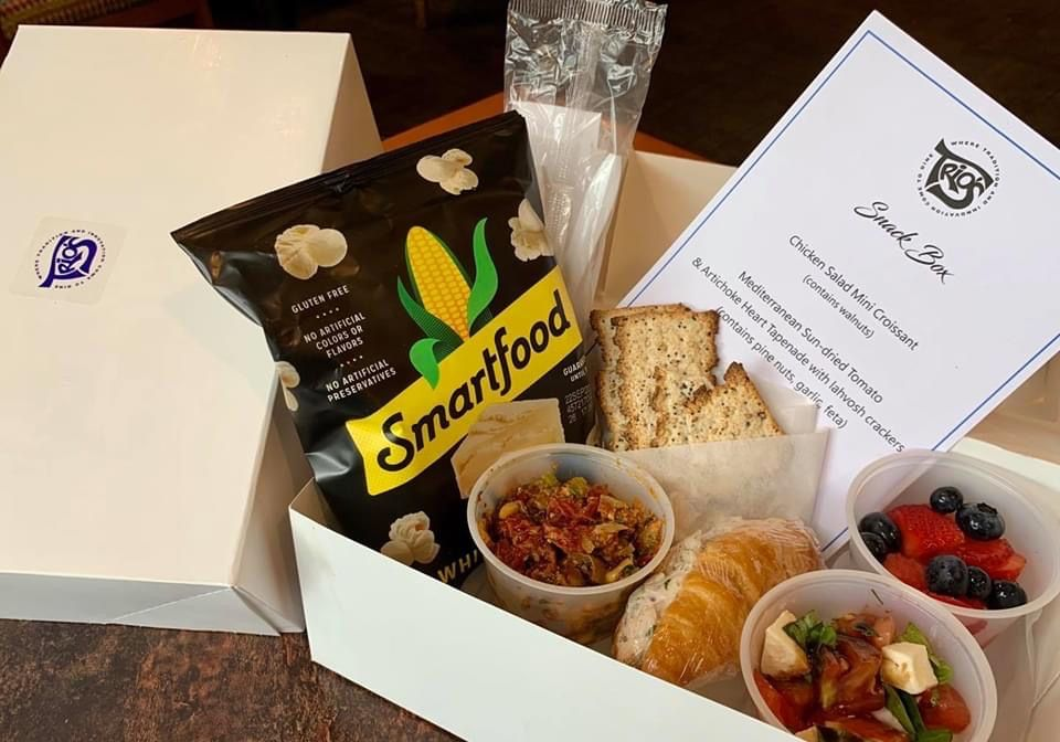 A photograph of a cardboard take out box containing a chicken salad croissant, tapenade, and other foods with a Trio's restaurant card
