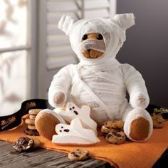 A photograph of a teddy bear dressed as a mummy surrounded by Halloween treats.