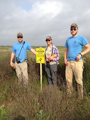 Pete Deichmann, Stephanie Bilodeau, and Joe Lippert with the symbolic fence