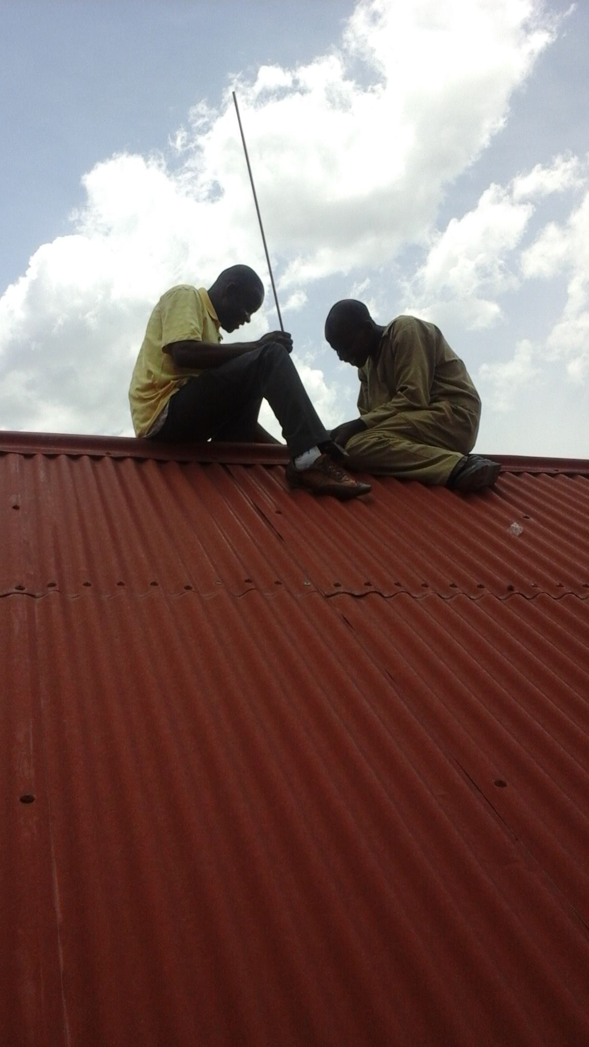 Installing lightning rods - called 'arrestors' by Ugandans