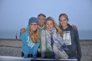 The Sturz Family smiling at the camera in front of a beach