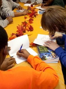 Student writers sign copies of their newly published poems.