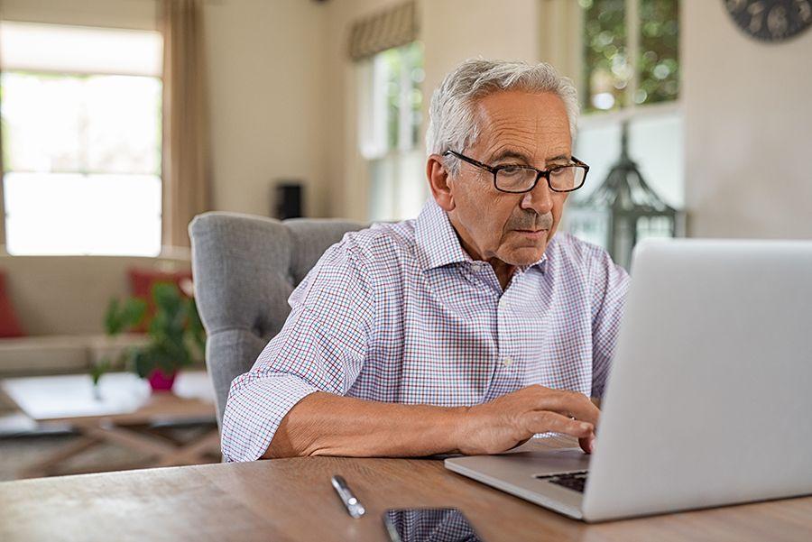 Older man sitting at home, online on his laptop