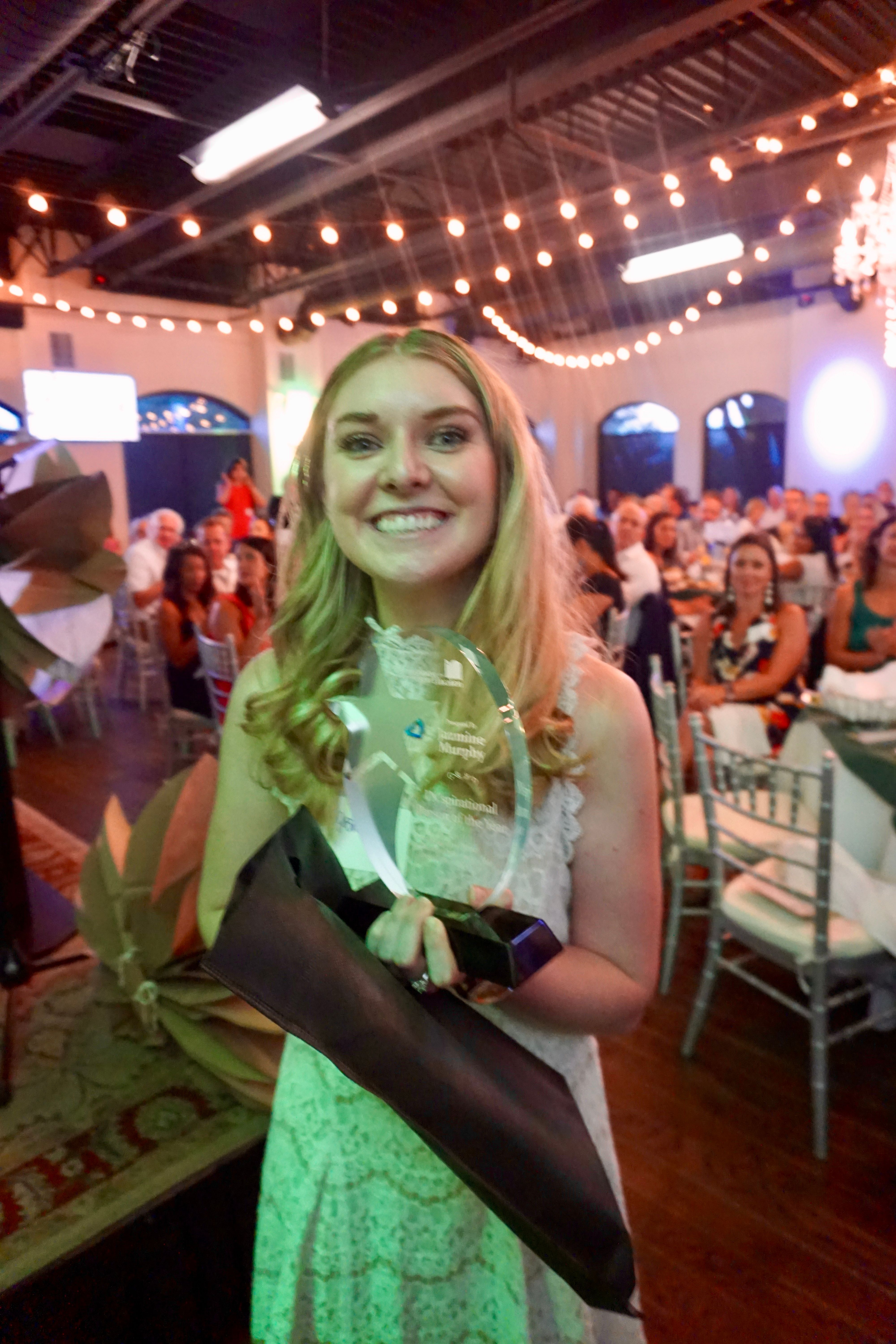 Jazmine stands in banquet room holding an award