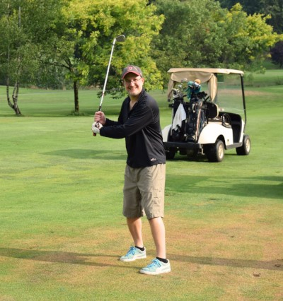 Jeff poses with golf club in front of golf cart