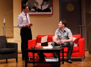 (L-R): Nick is standing and wearing a purple shirt with black slacks and a tie. He's talking to Terry who is sitting on a couch and wearing business casual attire. He's looking up towards Nick and listening to what he's saying.