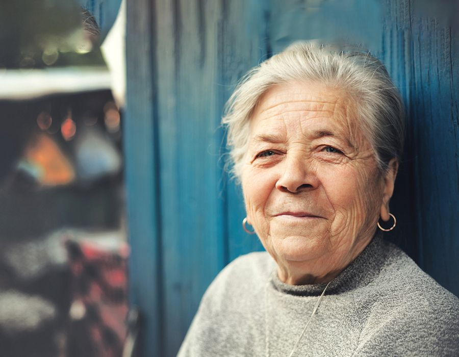 Older woman standing outside and smiling gently