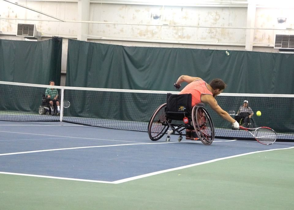 Adults in wheelchairs playing indoor tennis