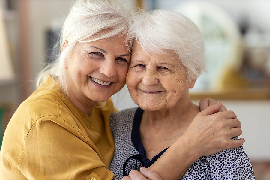 A smiling older woman hugs her caregiver in the front yard.