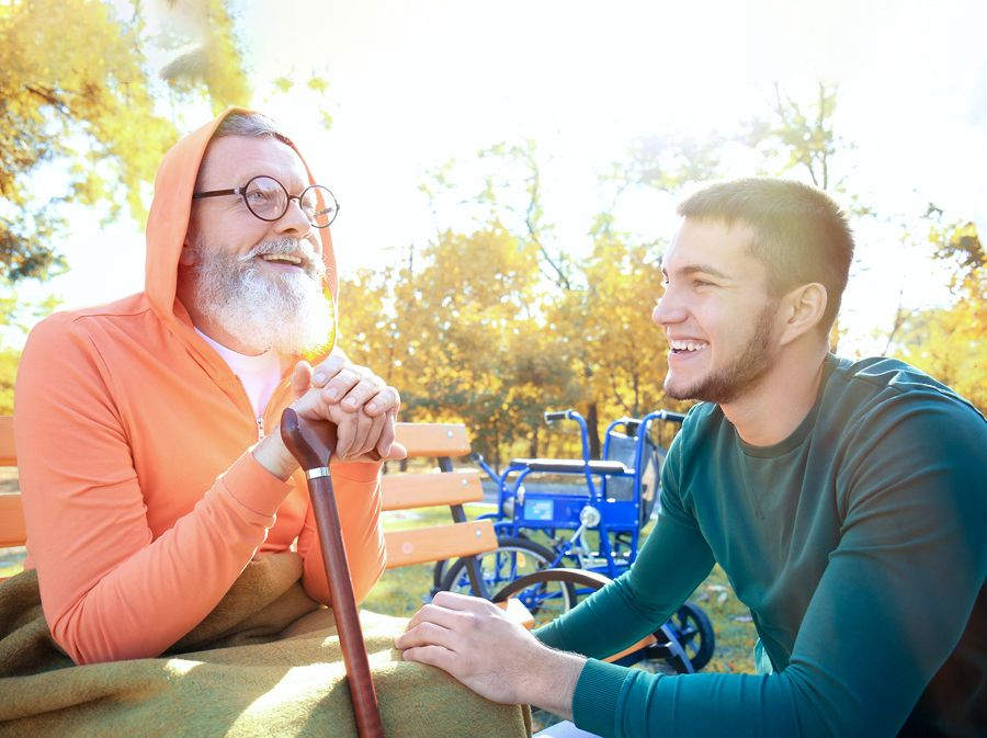 Smiling older man with cane is sitting on a park bench in front of his wheelchair. A young man crouches in front of him and is also smiling.