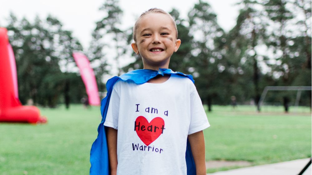 "Young child smiling, wearing a blue cape and white t-shirt with the words ""I am a Heart Warrior"" on the front."