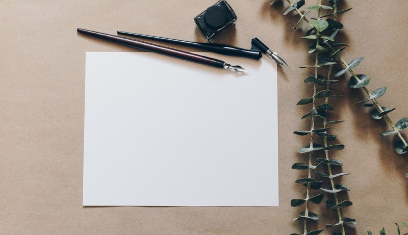 Sheet of blank paper and quill pen for writing newsletter
