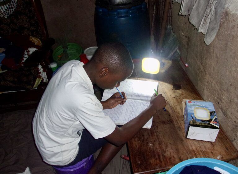 Boy doing his homework with a lamp.