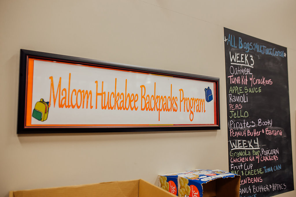 "Sign that reads, ""Malcom Huckabee Backpacks Program"" with yellow and blue backpacks in the corner."