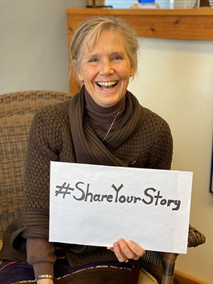 Michele Erikson, Executive Director, holds sign that says #ShareYourStory
