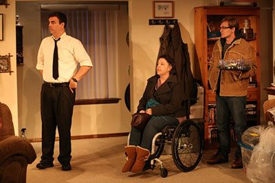 (L to R): David is standing, wearing a white shirt with a black tie, Jamie is in a wheelchair wearing jeans and purple shirt, and John is standing in a corner wearing a brown jacket. They're in a house grieving over their friend.