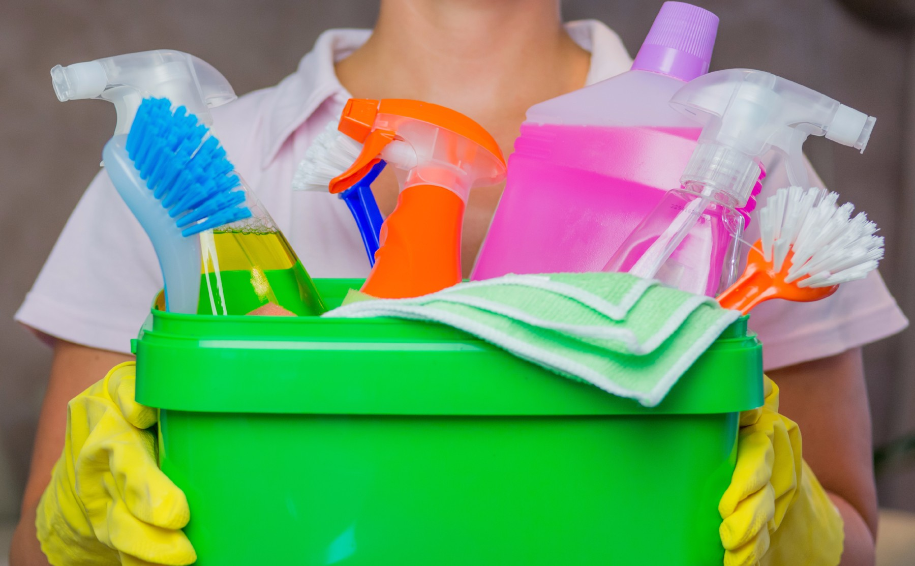 woman holding a bucket full of spring cleaning supplies
