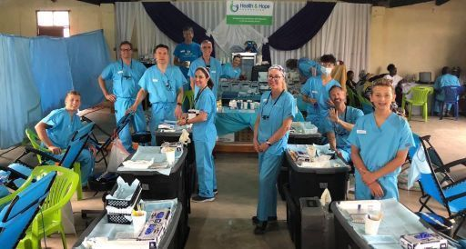 Group of people in a clinic wearing blue scrubs.