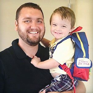 A father of a child with Down syndrome carries his son with his school backpack.