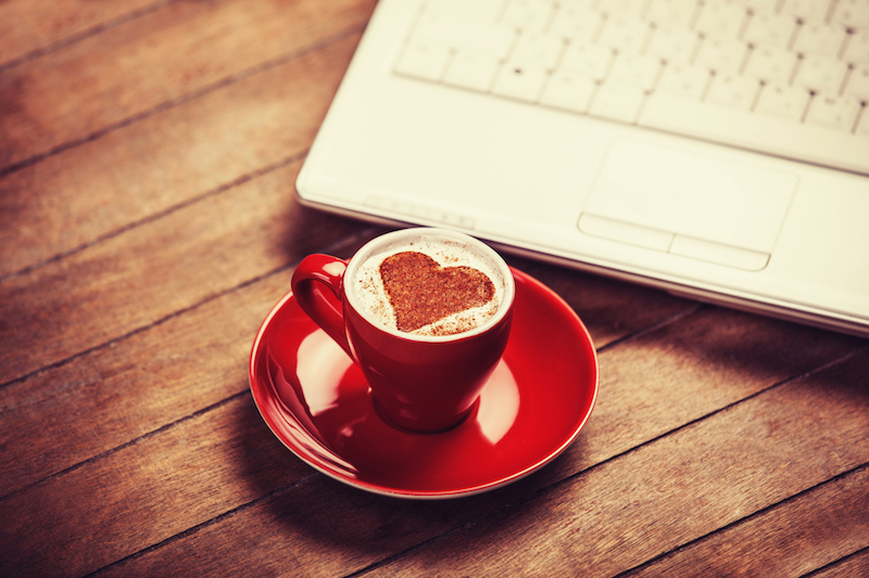 Cappuccino with a heart made of cinnamon and a laptop
