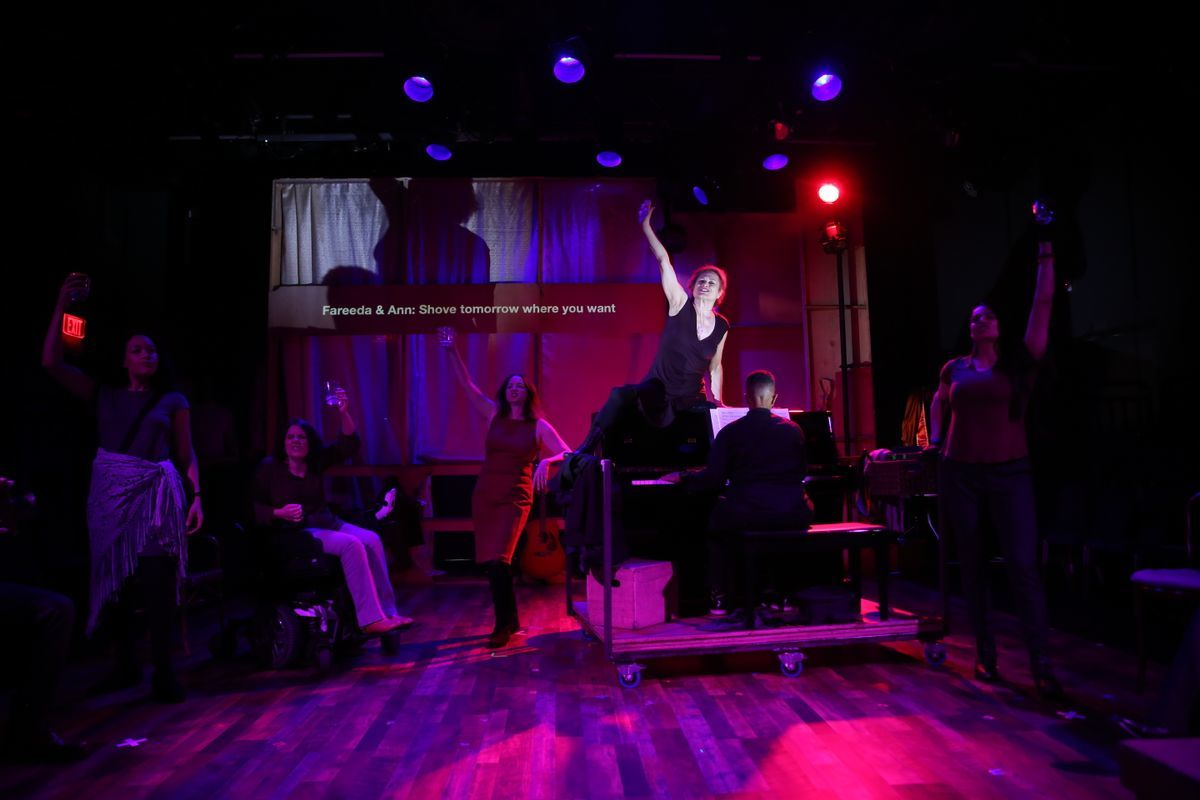 A picture of the cast of Brecht on Brecht during the bar scene. Everyone is standing and sitting, and they are raising their glasses and singing to something. The music director is playing on the piano.