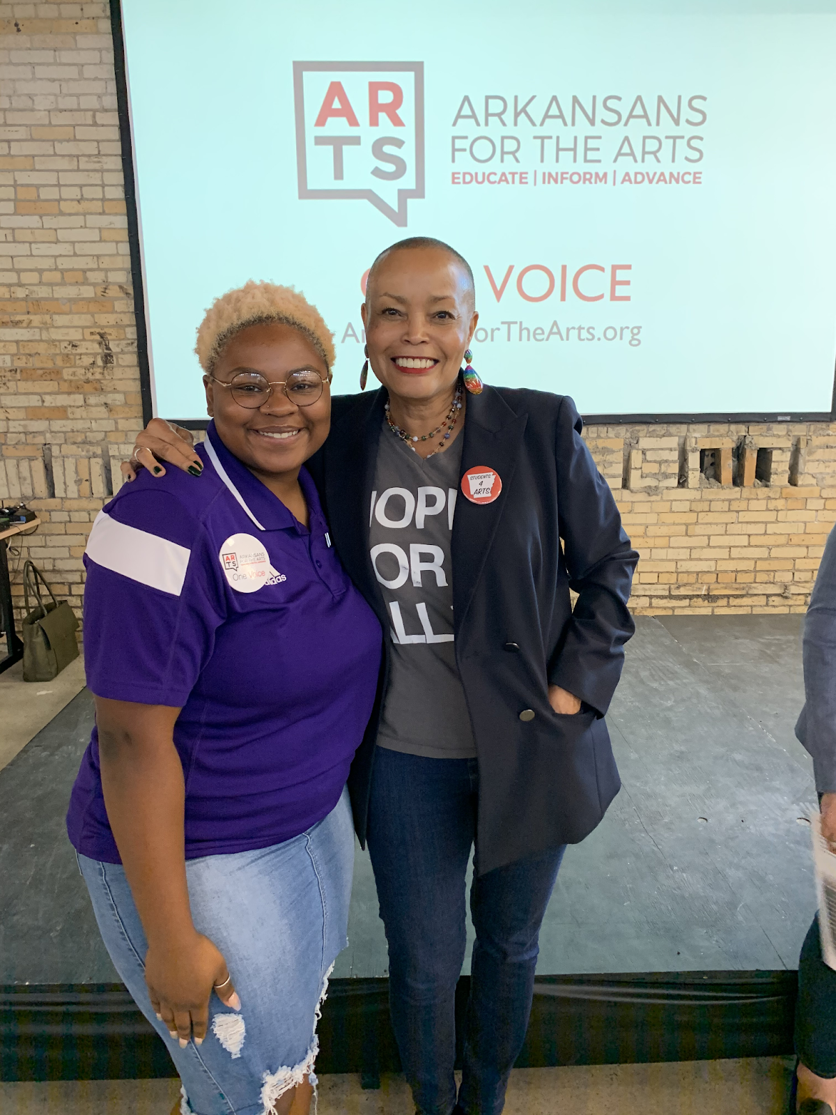 A college students in purple UCA shirt poses with state senator Joyce Elliot in front of a projector screen with the Arkansans for the Arts logo displayed prominently.