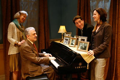 The majority of the group are standing around a piano and singing. George is sitting at the piano and playing it while Melanie is resting her hand on his shoulder. It looks like they are having a great time.