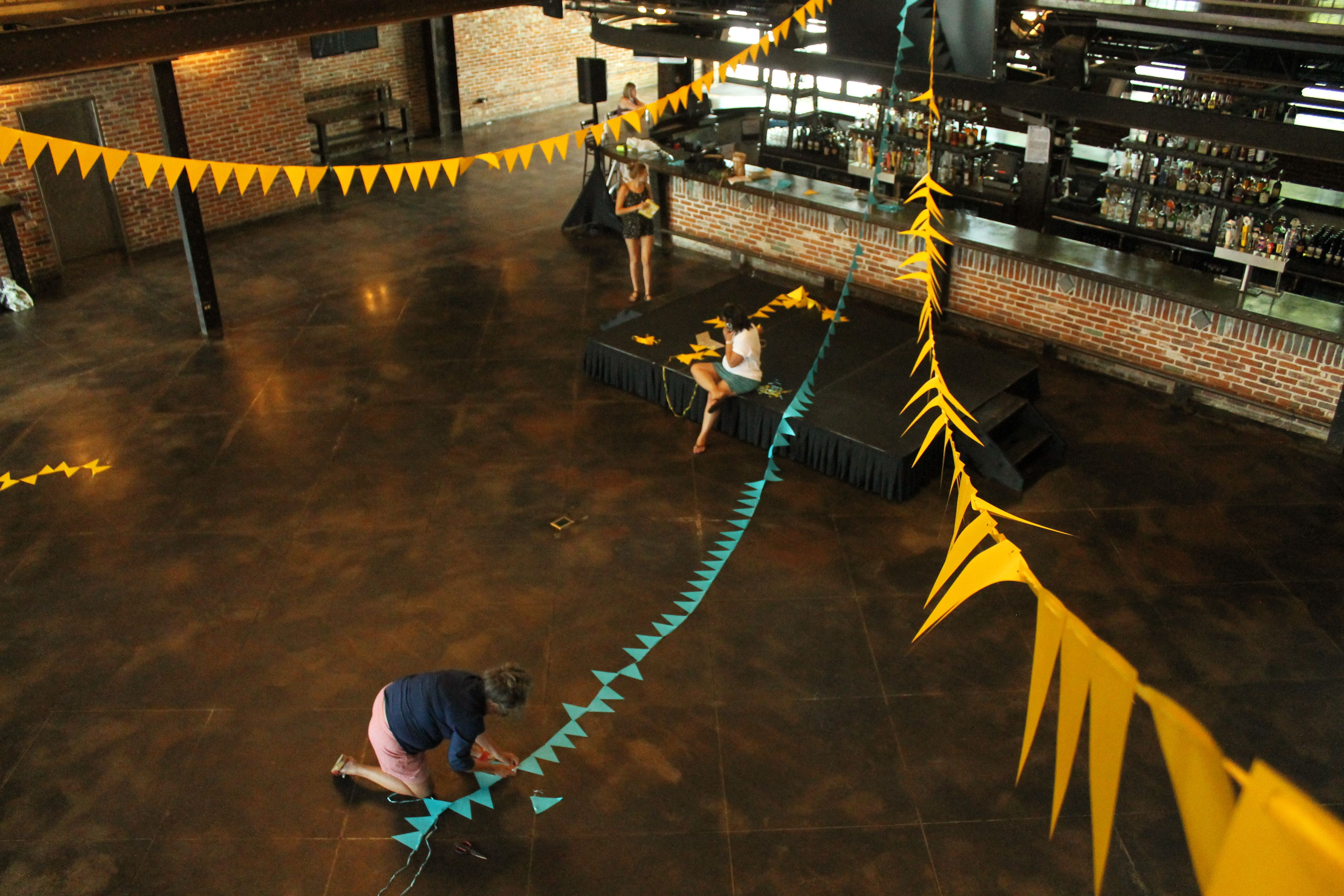 Woman kneels on ground; she is putting together yellow and turquoise flags, some of which hang from the ceiling above her