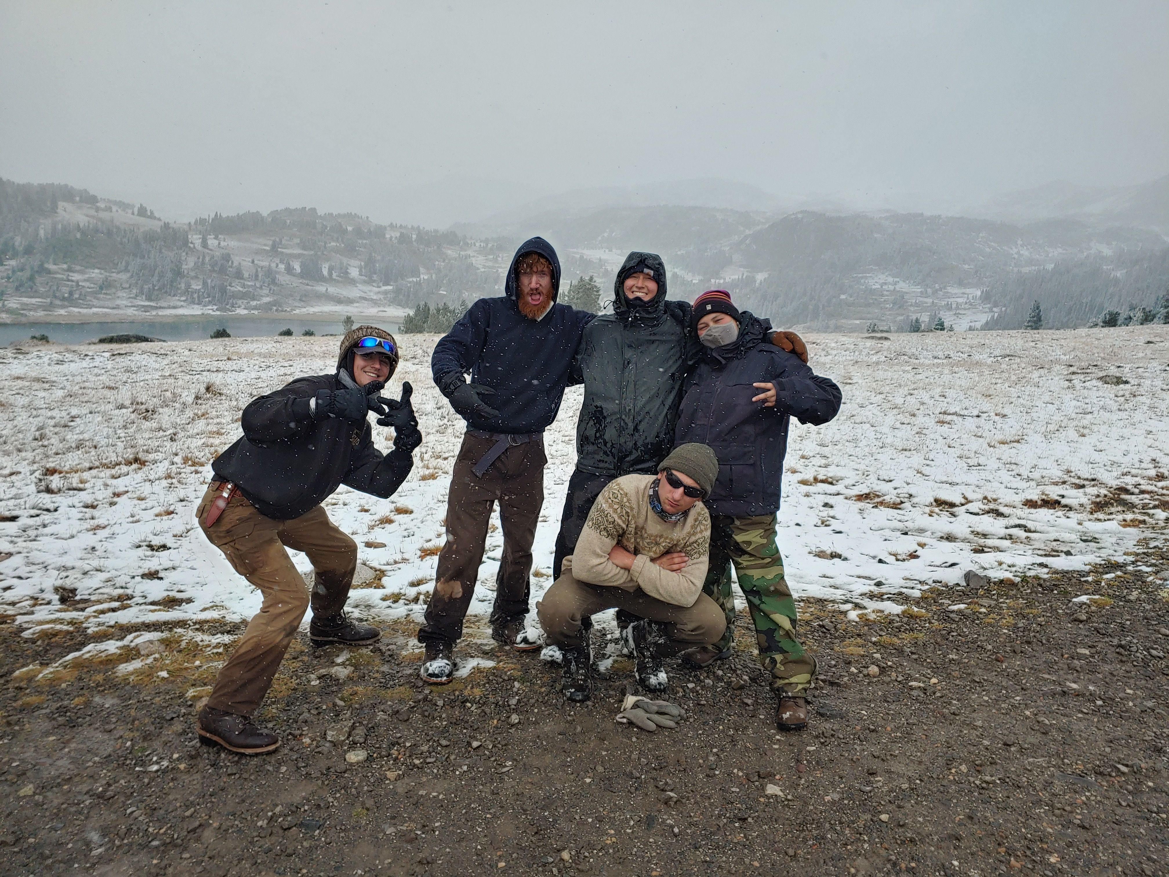 A crew poses, all bundled up in front of a snowy lake.