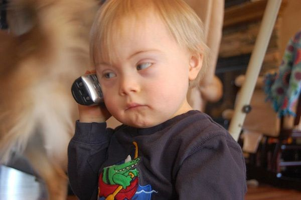 Toddler boy with Down syndrome holds cell phone up to ear to talk.