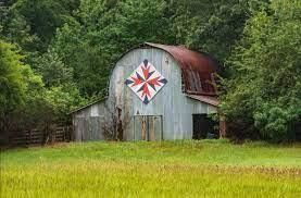 A weathered barn stands in the middle of a field of green grass. Hung prominently above the doors is a brightly colored quilt block of epic proportions.