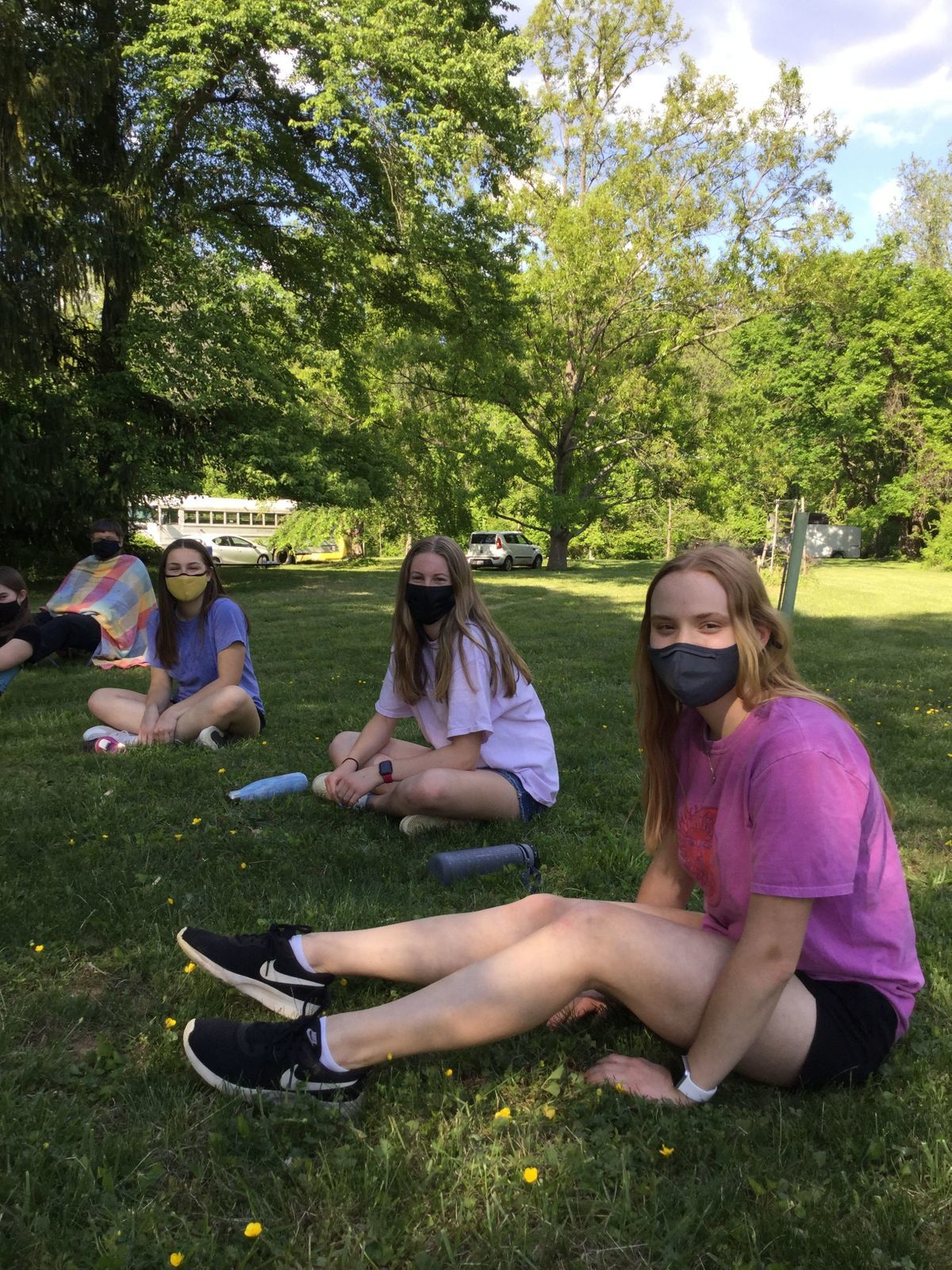 3 YFs sit smiling with masks on