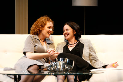 Marilee Talkington has red hair and wearing a grey suit. Pamela Sabaugh is wearing a grey sweater and a black suit and she has brown hair. They are both sitting on a couch and holding hands with smiles on their faces.