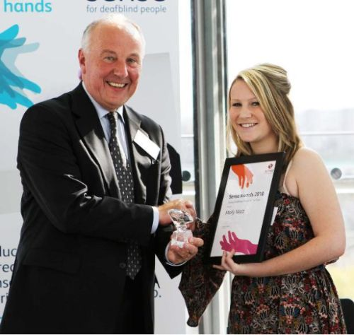 A picture of Molly Watt accepting her Young Deafblind Person of the Year Award. Watt is shaking the hands of a man while she holds her plaque and he holds her award.