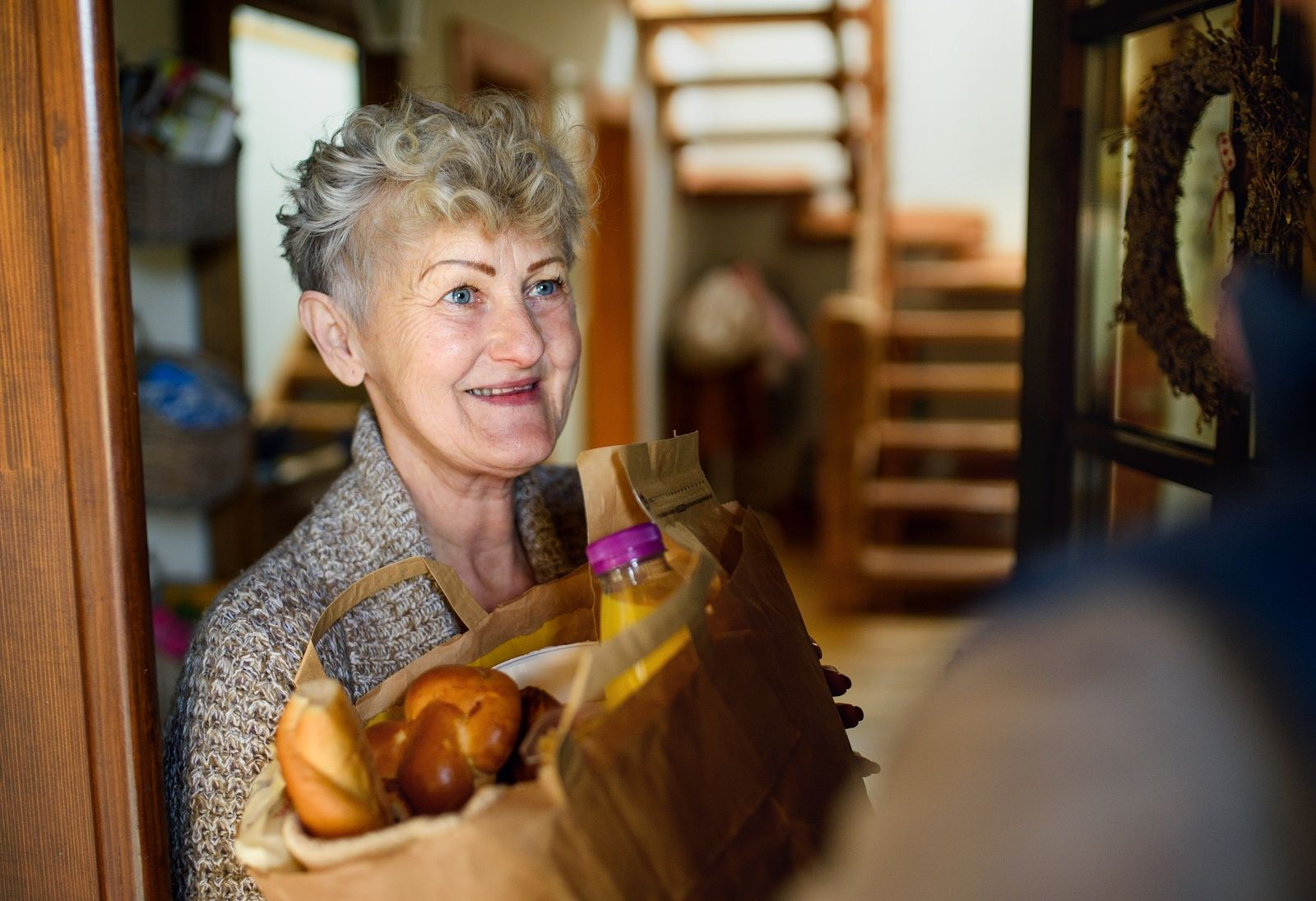 Older woman at her front door, smiling, holding groceries that were delivered