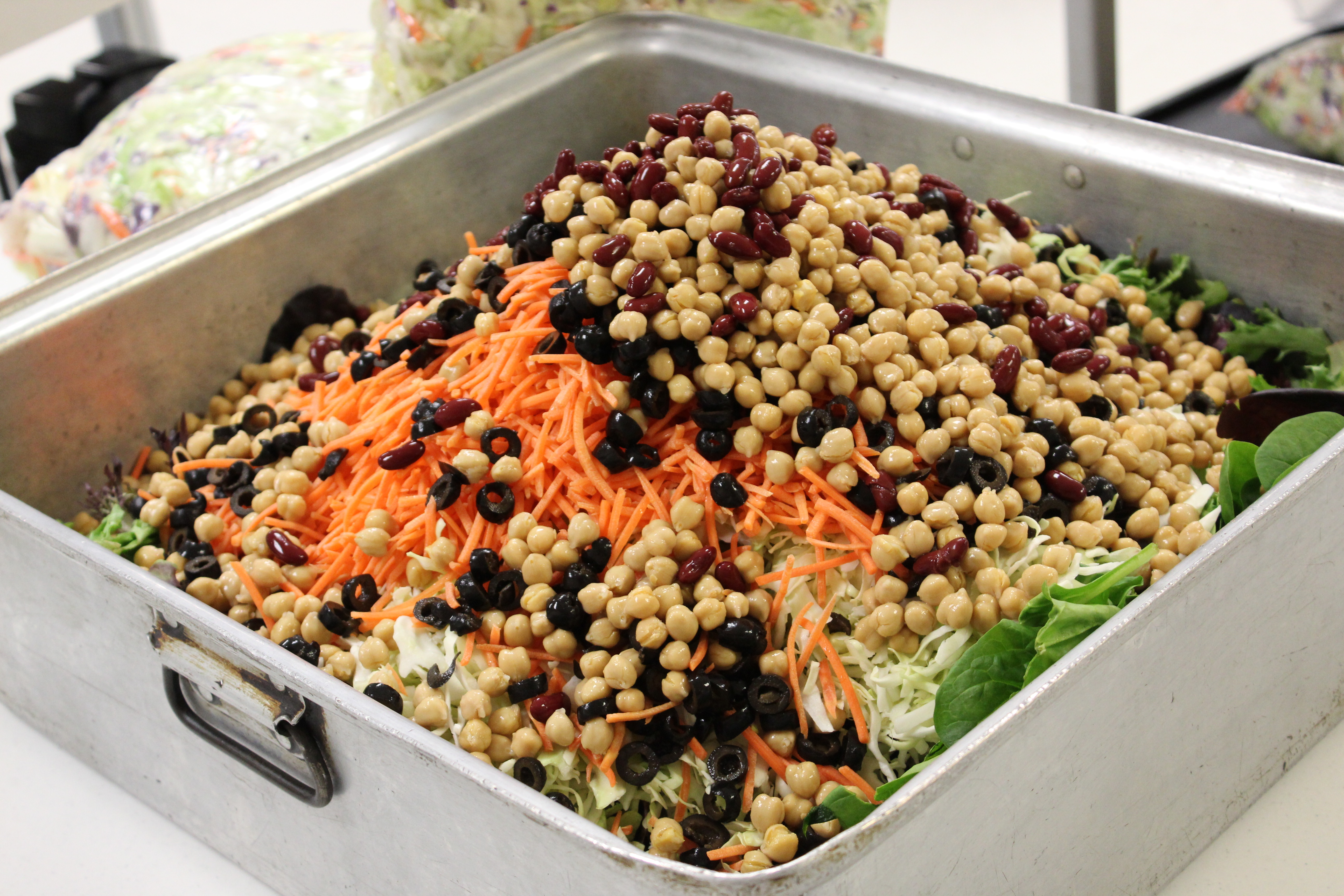 Pictured: Salad ingredients being prepared on a stainless steel table in the Senior Center kitchen.