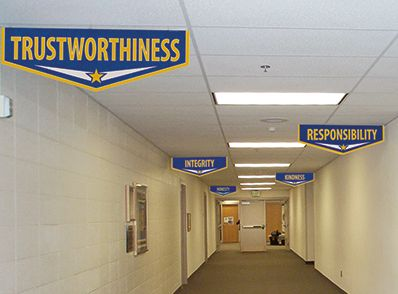 Custom Banners hanging in school hallway, character values words, blue and yellow, school banners