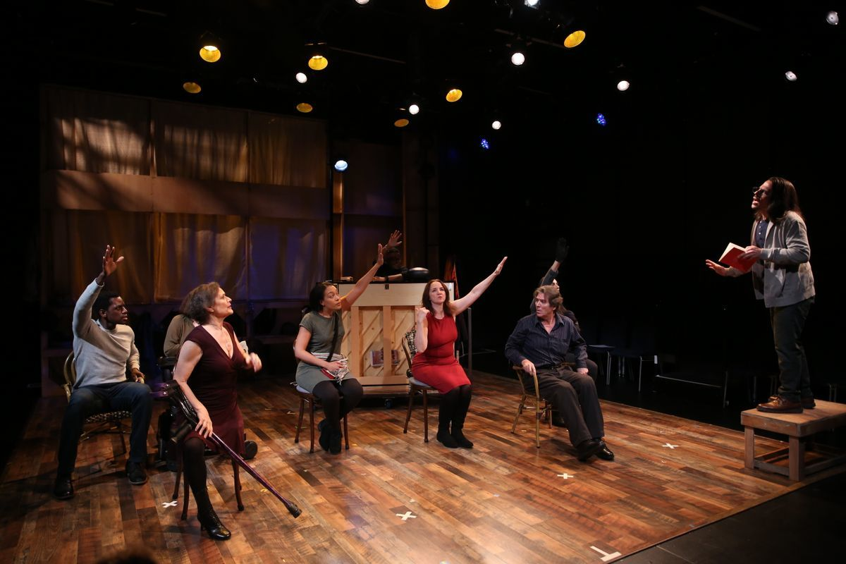 A picture of the cast of Brecht on Brecht, everyone is sitting and raising their hands. The only one is standing is Stephen Drabicki and he's standing on a step stool. He's holding a red book and asking the group a question.