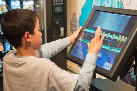 Young visitor at the National Cryptologic Museum discovers the Cipher Express Interactive Video Exhibit