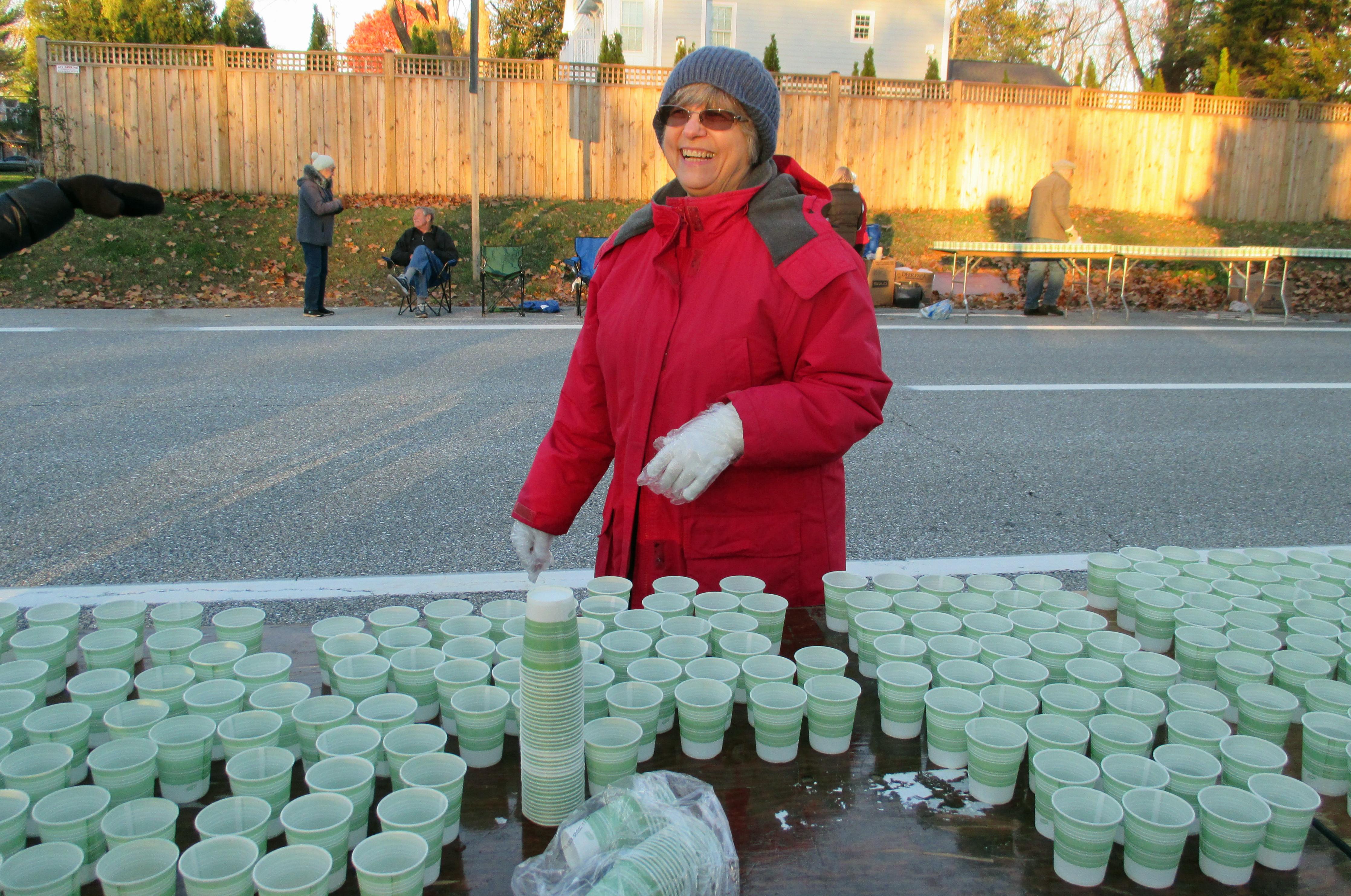 Maryland Branch volunteer Ellen Phipps fills water cups for Half-Marathon Runners.